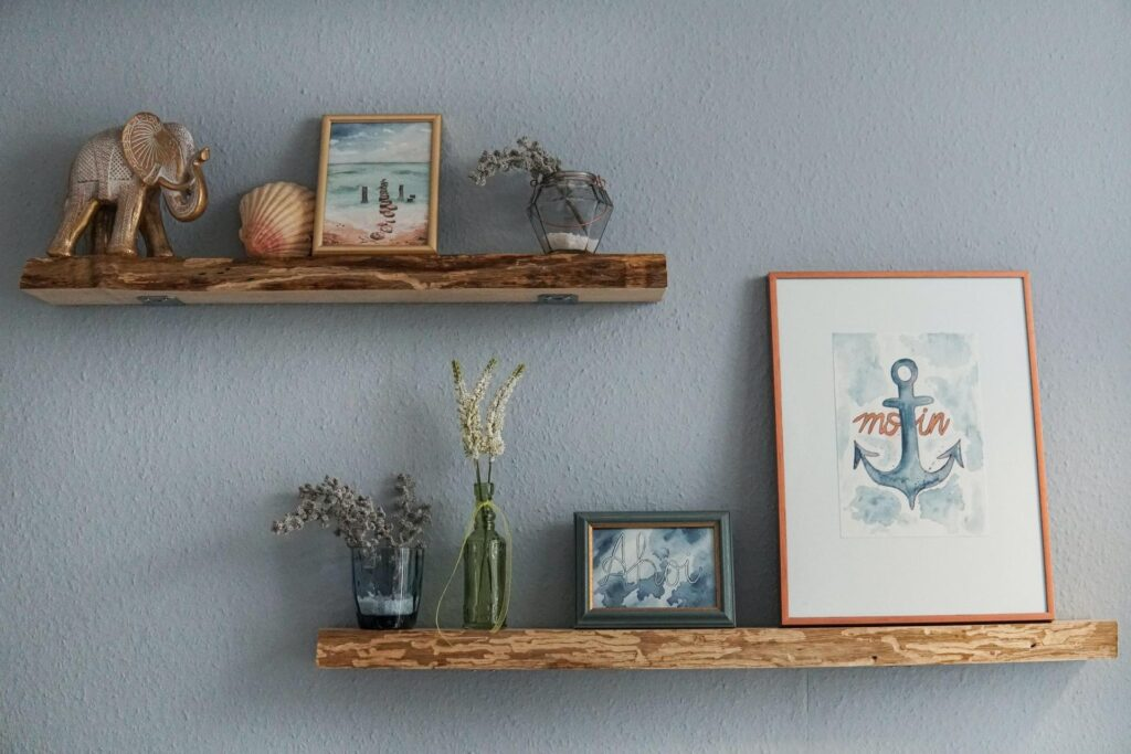 Two wooden shelves with an anchor painting, a glass vase, and a seashell
