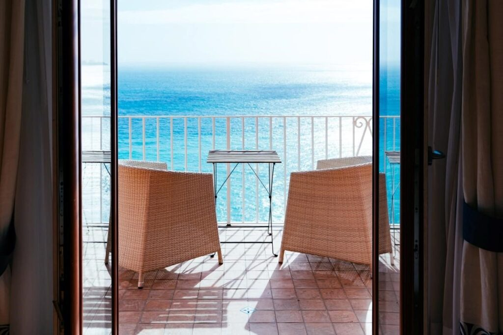 Two wicker chairs on a balcony overlooking the ocean